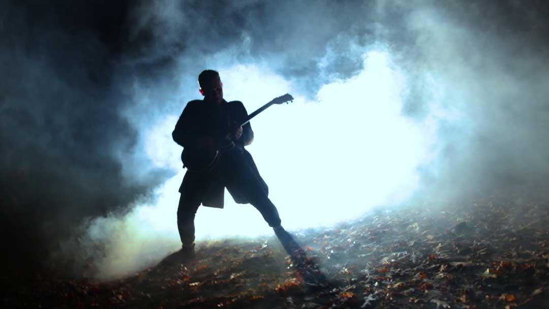 Ein Mann mit Gitarre nachts im Nebel im Wald