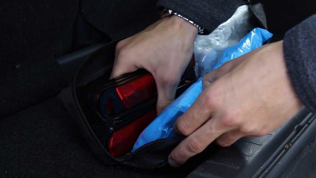 Eine Person holt ein Warndreieck aus dem Auto