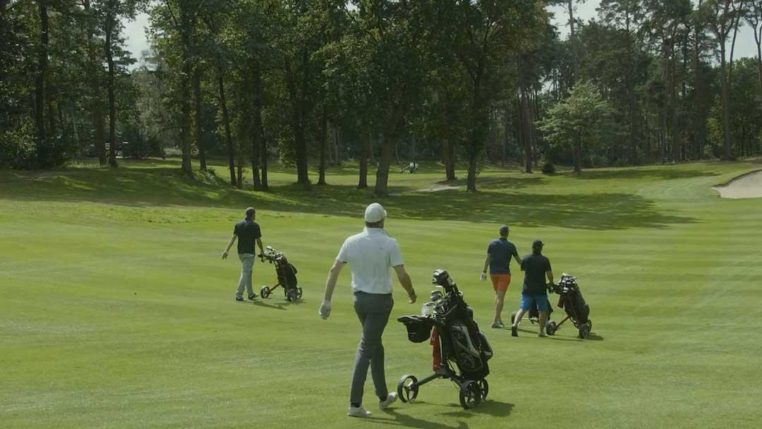 Golfspieler mit Golftasche auf dem Weg zum nächsten Abschlag