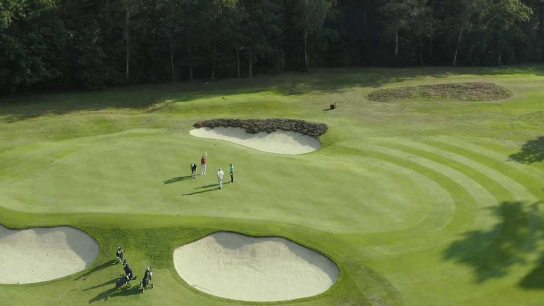 Luftbild eines Golfplatz mit mehreren Bunkern und vier Spielern
