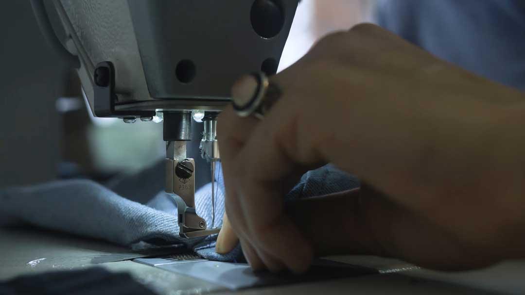 Eine Jeans wird in einer Nähmaschine von einer Hand geführt