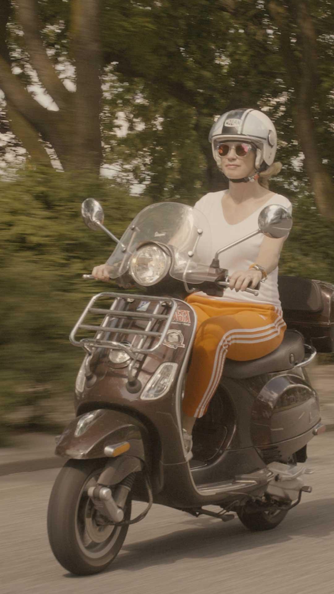 Frau auf Roller bei der Fahrt