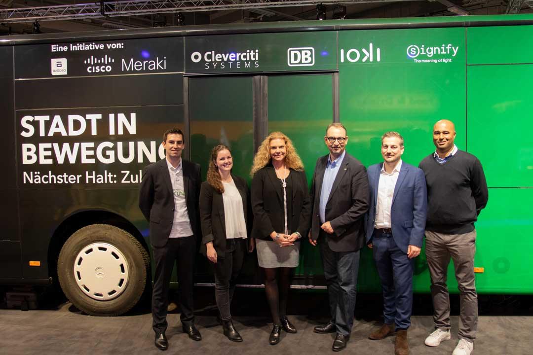 Sechs Personen vor einem folierten Bus
