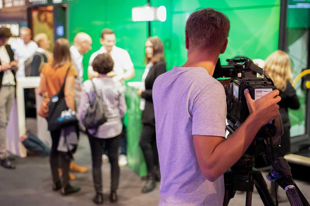 Mann mit Kamera filmt Veranstaltung